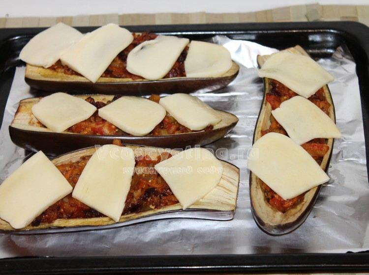 Накройте фаршированные баклажаны ломтиками сыра