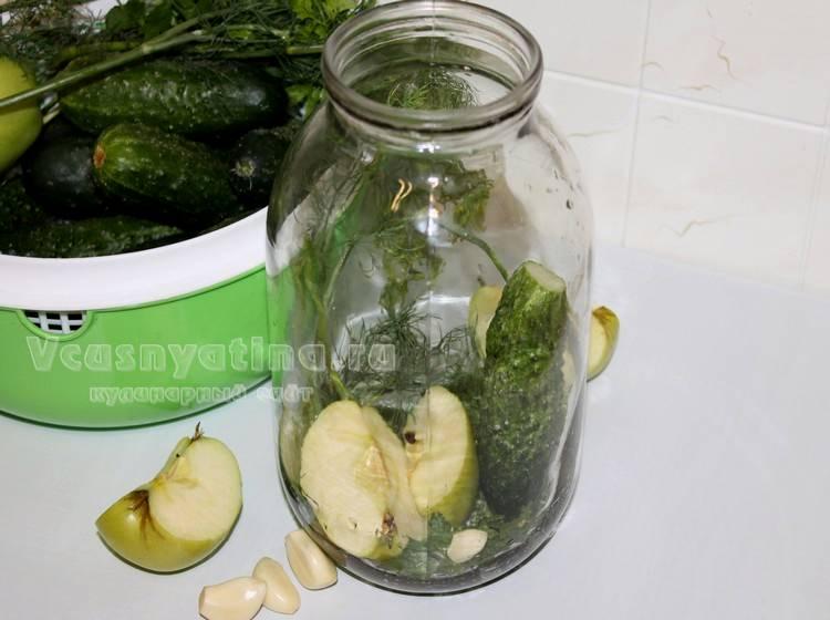 В чистую банку положите зелень и чеснок, добавьте яблоко