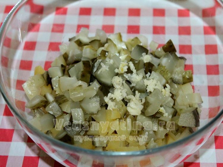 К картофелю добавить нарезанные огурцы и чеснок