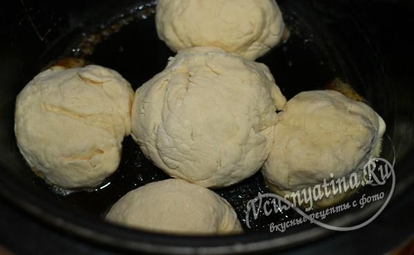 разделите тесто на 5-6 частей и выложите булочки в чашу мультиварки, смазанную сливочным маслом, оставляя место между ними