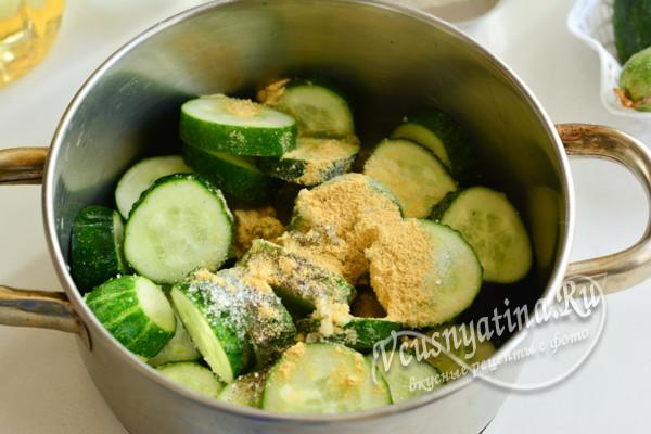 в емкость поместите огуречные колесики, добавьте измельченную чесночную массу, приобщите обычную поваренную соль крупного помола и сахар