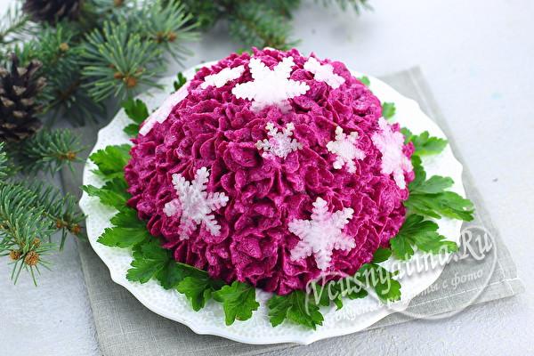 Салат с селедкой под кремом из свеклы, украшенный снежинками из редки